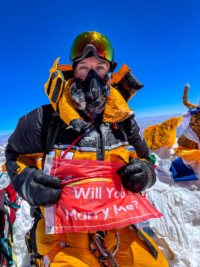 Andrew Hughes holds flag proposing to long-term girlfriend Lauren Beard on the summit of Mount Everest on May 23rd, 2021.