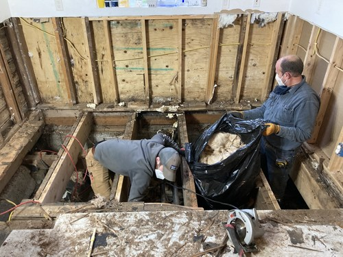 Ben Graf and his father removing mold and rat residue from the subfloor. Photo by Ben Graf.
