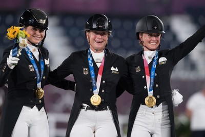 Germany's Dorothee Schneider, Isabell Werth and Jessica von Bredow-Werndl celebrating Dressage team gold at the Tokyo 2020 Olympic Games in Baji Koen Equestrian Park today.