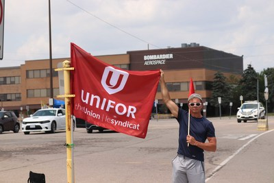 Unifor member with Unifor flag outside of Bombardier Aviation Downsview plant (CNW Group/Unifor)