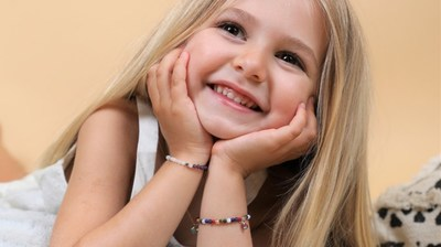 A young model wears the new Karma Kids jewelry collection from Karma and Luck.