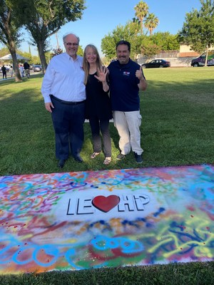 IEHP's Chief Executive Officer Jarrod McNaughton, Governing Board Member Eileen Zorn, and Community Health Senior Director Cesar Armendariz visited the Los Amigos neighborhood to support the project and paint an IEHP logo on one of the sidewalk paths.