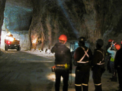 Three miners underground looking down a dark tunnel at a truck operating on the wall of a mine. Photo credit Derrick Midwinter (CNW Group/Unifor)