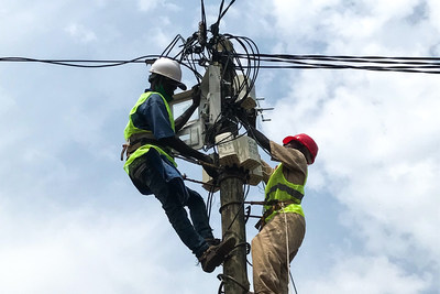 Microgrid operators installing SparkMeter metering equipment on a distribution line.