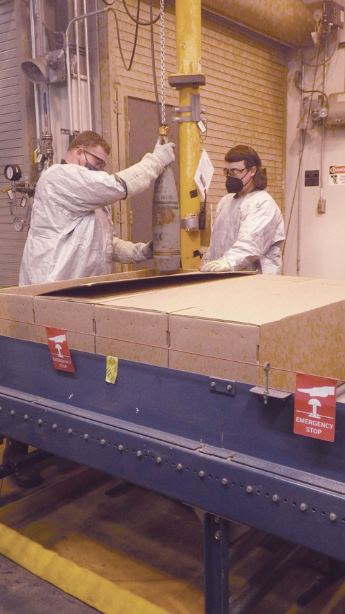 A munitions handler places a 155mm projectile containing mustard agent into a box to begin the destruction process in the Static Detonation Chamber at the Blue Grass Chemical Agent-Destruction Pilot Plant.