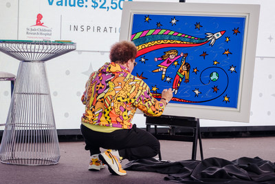 Britto paints an original art piece live during a private dinner surrounded by vintage planes in a hangar in Cape Canaveral, Florida, on Sept. 14 to be auctioned off on CharityBuzz.