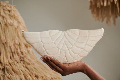 """Beamina's ZER: Angel' Wings Handbag in ivory. On the background: """"Suspiros"""" created by artist Frances Rivera and part of Museo de Arte de Puerto Rico's collection."""