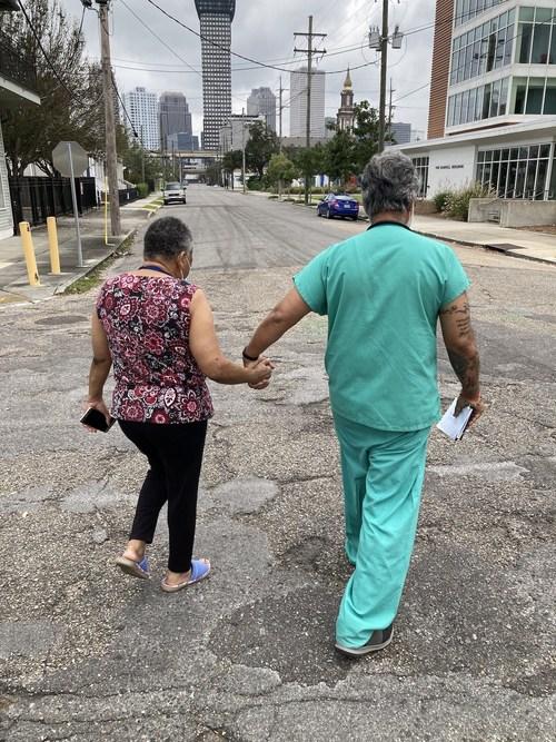 Dr. Vijay Jaligam, JenCare Senior Medical Center, helps a senior during the aftermath of Hurricane Ida walk across a New Orleans street.