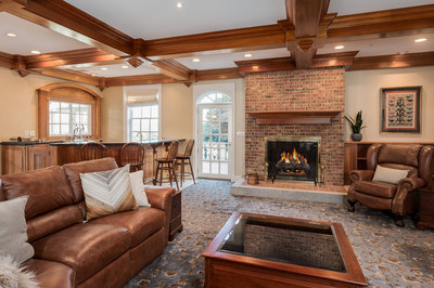 This cozy living area provides direct access to the indoor pool. A wood-burning fireplace offers charm, while a wet bar with an old-fashioned soda fountain dispenser adds a touch of whimsy.  NewHampshireLuxuryAuction.com.