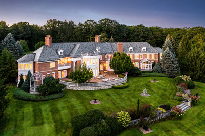 A sprawling patio overlooks the property's neatly manicured lawns and serves as an excellent space for both quiet relaxation or celebrations on a grand scale. Mature landscaping around the estate augments its privacy. NewHampshireLuxuryAuction.com.