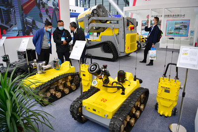 Visitors learn about various kinds of mining robots at the exhibition. (PRNewsfoto/The People's Government of Yulin City)
