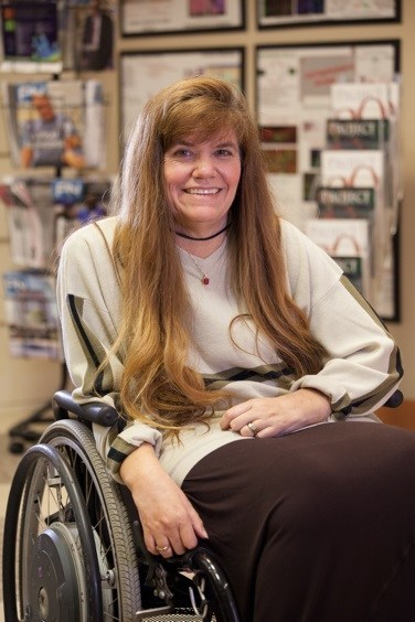 Image description: Kim Anderson-Erisman, PhD, a white woman with long, light brown hair, sits strapped into her manual wheelchair, wearing a light shirt with striped long-sleeves and documents hanging on the wall behind her.