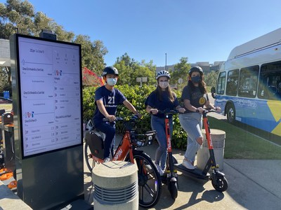 UC San Diego students next to Spin Hub, where a live map of bus locations (powered by TransLoc technology) are displayed.