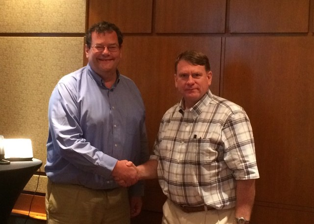 John Day, CEO of TechInsights and Terry Ludlow, Founder and Chief Executive of Chipworks shake hands as news emerges of their newly combined businesses.