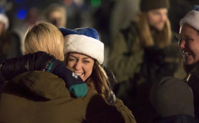 Une employée de WestJet serre dans ses bras une résidente de Fort McMurray lors de la soirée « Flocon de neige » de WestJet. (Groupe CNW/WestJet)