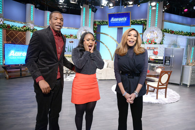 """Aaron's surprised winners of the """"Big Blue Bow Home Makeover"""" (L to R), Anthony Harper and Jasmine Dobbs with Wendy Williams, on Friday's Debmar-Mercury's """"The Wendy Williams Show"""" with a home makeover of new furniture, appliances and electronics. The Dobbs and their son were flown to the set of """"The Wendy Williams Show"""" under the impression they were merely finalists for the grand prize. They were shocked to learn they were the winners."""