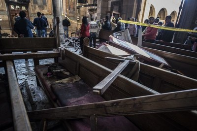 Egyptian security forces (L) inspect the scene of a bomb explosion at the Saint Peter and Saint Paul Coptic Orthodox Church on December 11, 2016, in Cairo's Abbasiya neighbourhood.