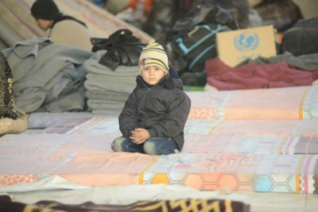 Le 7 décembre 2016,  un garçon est assis dans un entrepôt de Jibreen, en Syrie. Des milliers de déplacés ont fui les combats à Alep-Est. L'UNICEF procure des vêtements d'hiver, de l'eau potable, des soins de santé, de l'éducation et de l'aide psychosociale aux enfants qui ont vécu l'horreur de la guerre.© UNICEF/UN043364/Rzehak (Groupe CNW/UNICEF Canada)