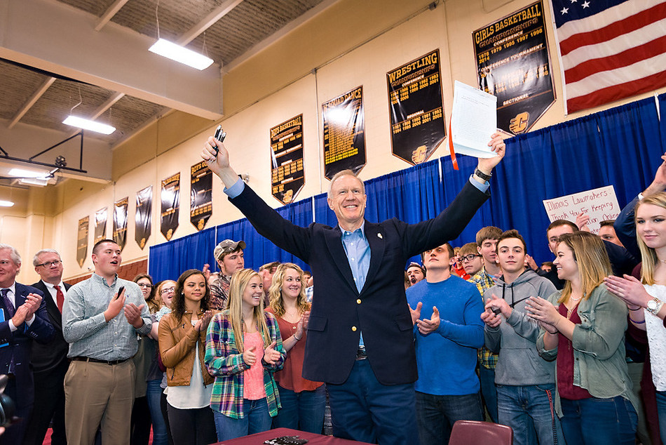 Illinois Gov. Bruce Rauner holds up the signed Future Energy Jobs Bill at an event at Clinton High School on Dec. 7. Photo by Ed Cicenas, EMC Photography