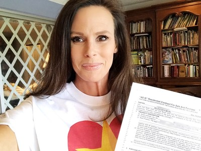 Holding a copy of the contract for the Gold Star family's new home