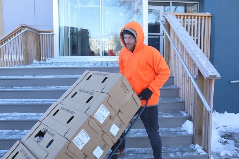 Joe, a resident of Grace Centers of Hope's 1-year Life Skills program, unloads 100 turkeys gifted by sunroof supplier Webasto North America.