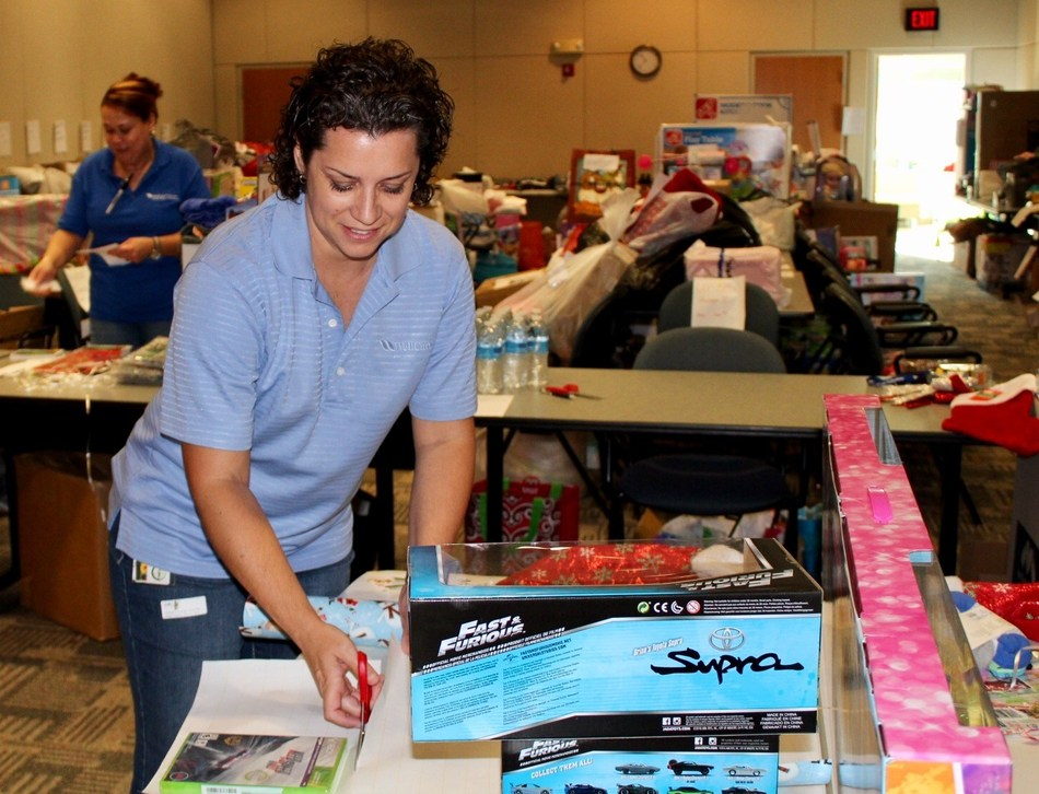 "A WellCare associate wraps gifts as part of WellCare's ""Santa Cause"" initiative."