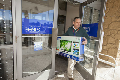"""A Sears associate delivers an online purchase to the car of a member who used the In-Vehicle Pickup service. Sears announced a last-minute shopping incentive of 20 percent off Sears.com Dec. 20-24 for members who choose free store pickup for their purchases in select product categories and use the promo code """"JINGLEBELLS."""""""