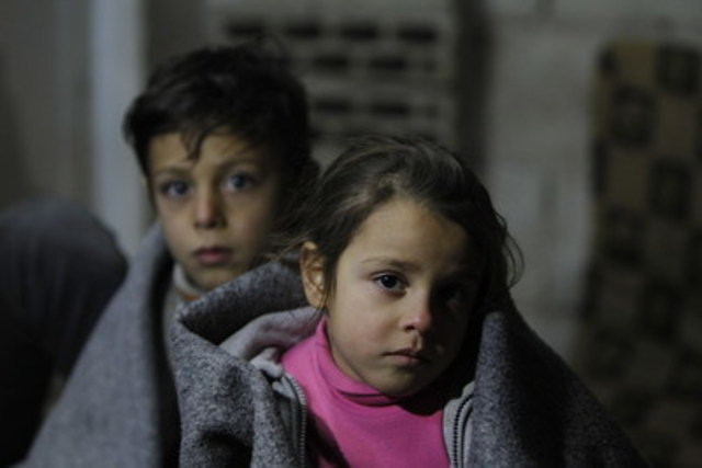 Ghinwa, 7, and her brother Alaa, 11, at the Al-Khalidia Al-Khamisa informal settlement in Homs, Syria. As their house in this unfinished building remains in dire condition and many repairs are needed to make it suitable for winter, Ghinwa and Alaa are trying to get warm with blankets. (C)UNICEF/ Syria 2016/ Sanadiki (CNW Group/UNICEF Canada)