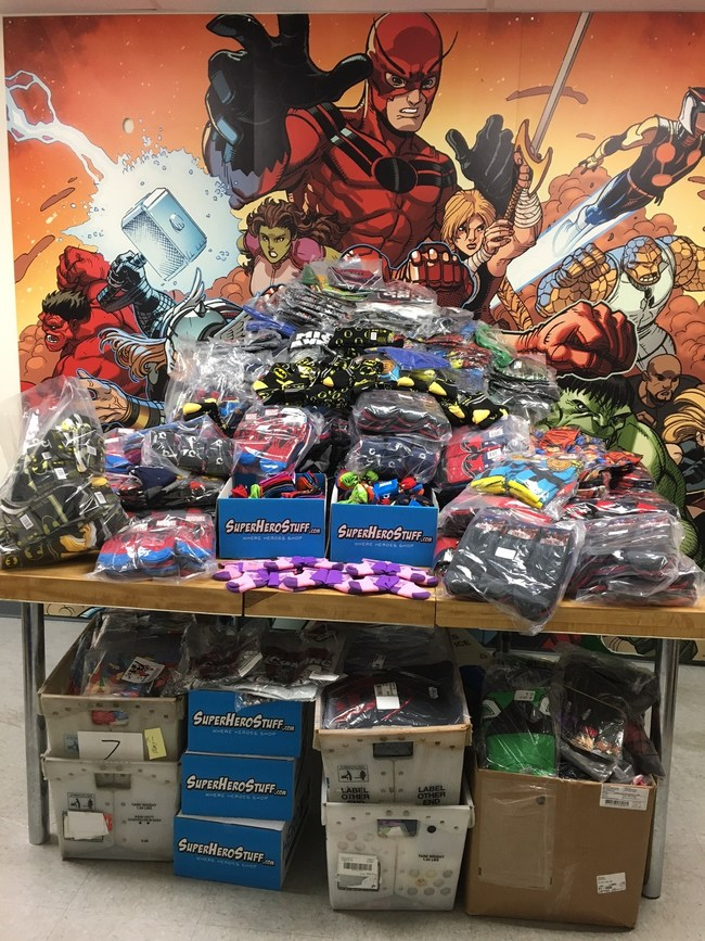 SuperHeroStuff's donation, totaling over 1,500 socks and 500 t-shirts, overflows on the table and shipping crates.