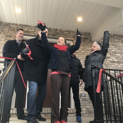"""St. Louis resident, first-time homeowner and single mom Latonia H. (middle) jumps for joy when presented with her new, fully furnished home with Steve Kincanon, Aaron's Vice President, and Kurt and Brenda Warner, founders of First Things First Foundation (FTFF). Aaron's, Inc. and Progressive Leasing, a division of Aaron's, Inc., contributed the furnishings on Friday during two surprise """"Homes for the Holidays"""" presentations with Habitat for Humanity Saint Louis, FTFF and U-Haul."""