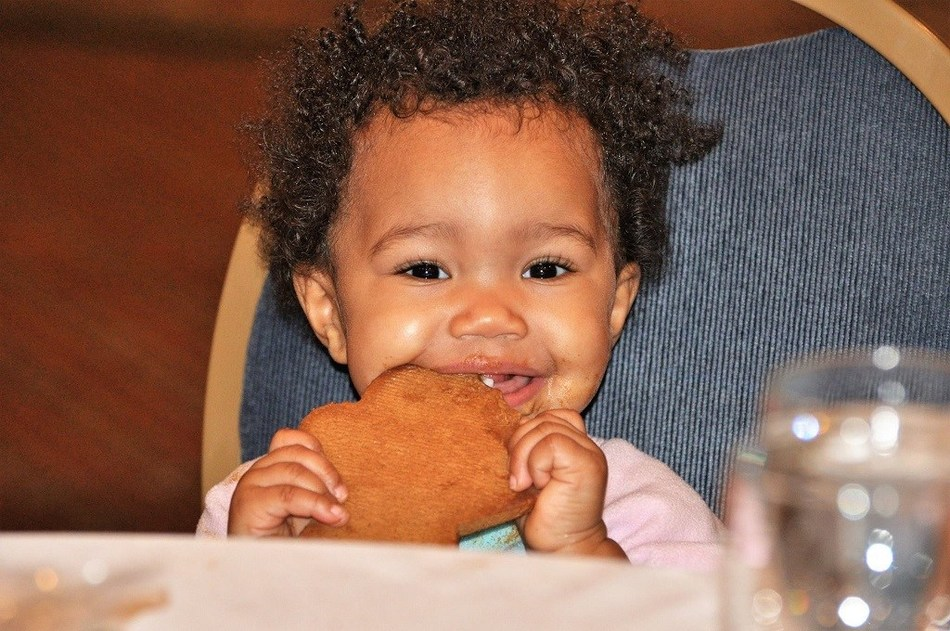 Holiday pleasures: This little one had a blast at the Wounded Warrior Project(R) holiday connection event. She shows us few things are more joyful than biting into a delicious gingerbread cookie. Photo credit: Kimberly Hague