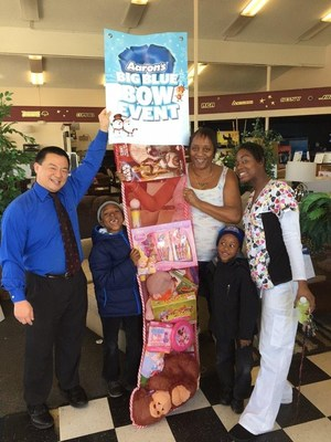(L to R) Aaron's General Manager Mark Yonemura, with California Grandmother Ophelia Blanchard, her daughter-in-law Sheila and two grandsons, proudly receive their giant stocking filled with toys.  Aaron's, Inc., a leader in the sales and lease ownership and specialty retailing of furniture, consumer electronics, home appliances and accessories, this December is giving away 1,435 giant stockings filled with toys and games to deserving families across the U.S.
