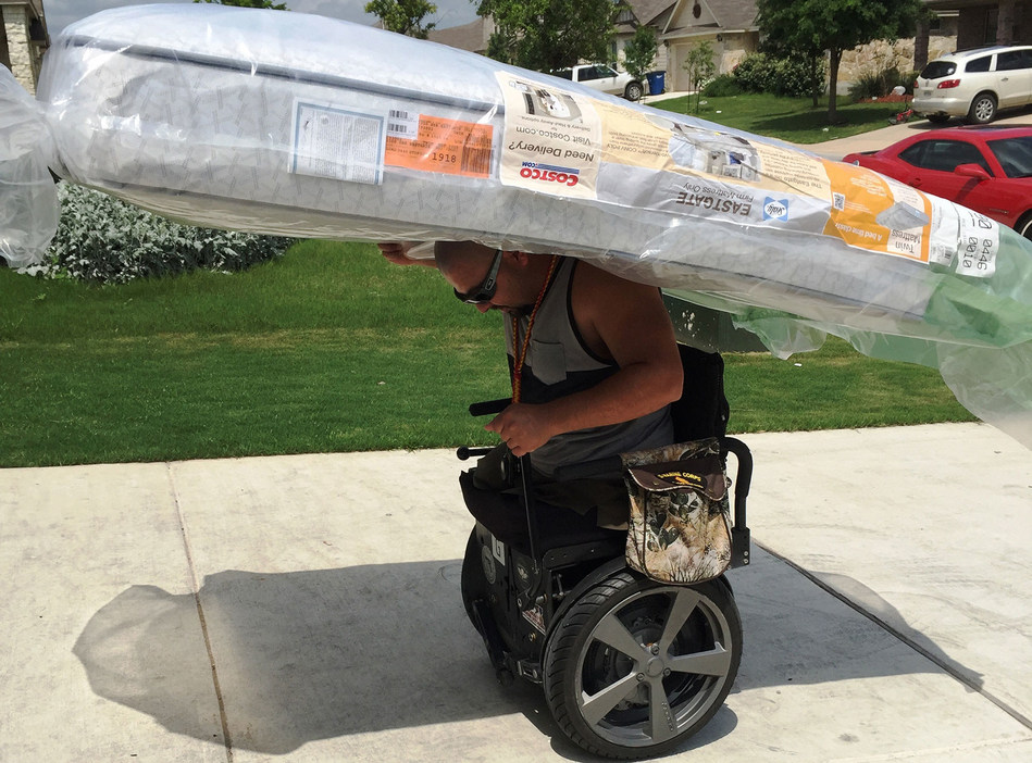 """Retired Marine Corps Gunnery Sgt. Guillermo """"TJ"""" Tejada uses his ALLY Chair to carry a full-size mattress into his home."""