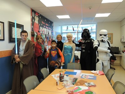 """Costumed characters from """"Frozen"""" and """"Star Wars"""" surprise young Jedi in training, Adan, with a Chewbacca plush toy during the """"Bear Hugs Toy Drive"""" donation at Miller Children's & Women's Hospital Long Beach."""