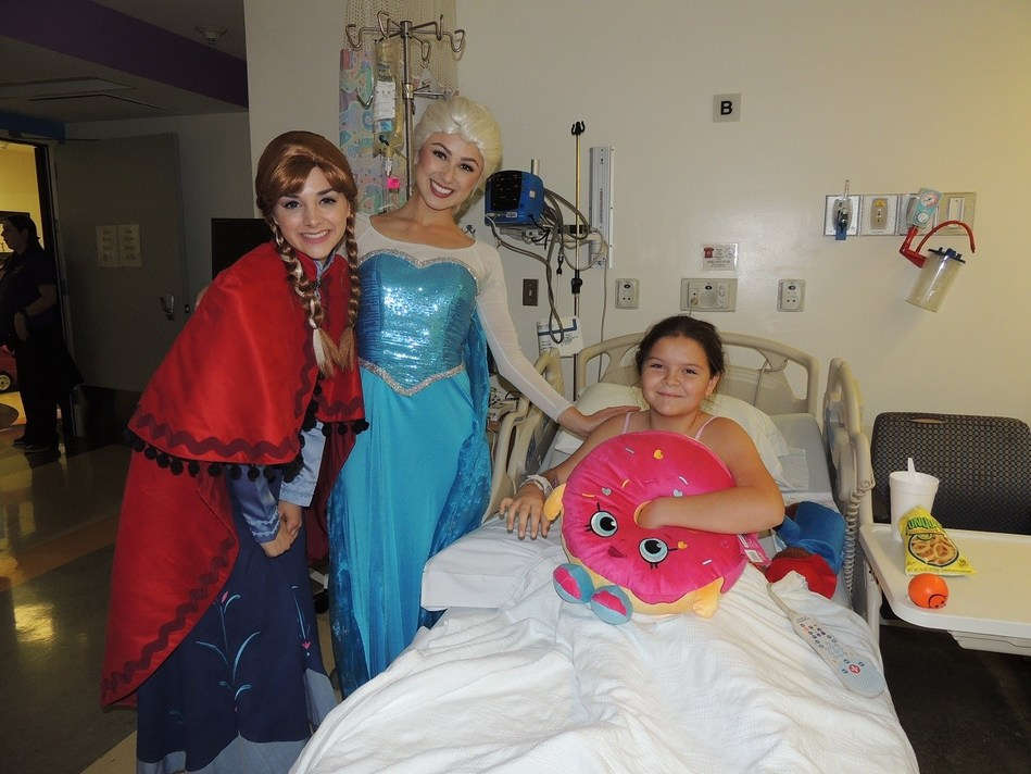 Costumed characters, Elsa and Anna from Frozen, spread holiday joy and deliver a plush toy to Miller Children's patient, Kayla.