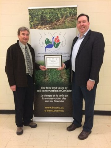 Adam Hayes (left) receives the L. B. Thomson Conservation Award from SCCC Chair, Alan Kruszel today at the SouthWest Agricultural Conference in Ridgetown, Ont. (CNW Group/Soil Conservation Council of Canada (SCC))