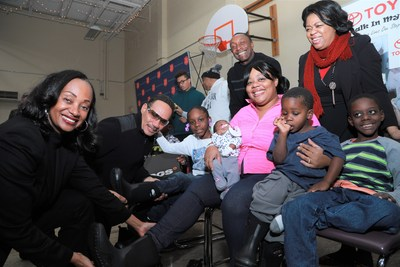 Toyota Donates Winter Boots and Socks to Detroit Families In Need - NAIAS (Alva Mason, Toyota, Ronnie McNeir of The Four Tops, Greg Jackson, owner Prestige Warren Toyota and Kyra from TSA Booth Shelter help families try on new boots.)