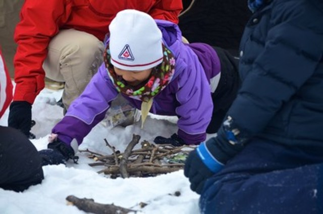 A young Scout practices her fire building skills during a winter adventure. Photo courtesy of Scouts Canada. (CNW Group/Scouts Canada)