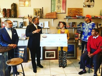 Freedom Ties Co-Founder Tavares Bethel presents a check to Maeva Jackson, founder of Black World Books, who received the majority votes which awards her half the sales generated from the December sales on FreedomTies.com.