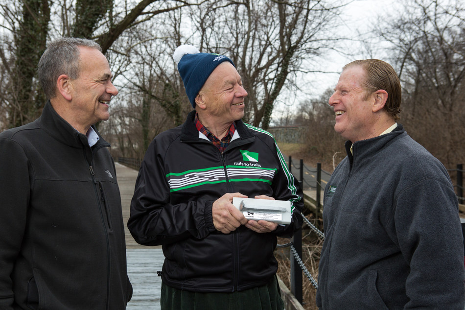 Rails-to-Trails Conservancy President Keith Laughlin (left) and Jeff Doppelt (right) present former Congressman Tom Petri (R-Wis.) with the 2016 Doppelt Family Rail-Trail Champions Award at a ceremony on Jan. 10, 2017 on the Mount Vernon Trail in Arlington, Va. Photo credit: Eric Kruszewski