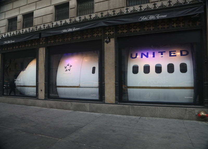 """United Polaris business class takes over the windows at Saks Fifth Avenue in New York City. Entitled """"Now Arriving,"""" the 14 storefront windows display a replica of a United Airlines plane. The center six windows feature a re-creation of the United Polaris business class experience, including actual United Polaris seats, which will debut on flights in February, and the cabin's custom Saks Fifth Avenue bedding suite."""