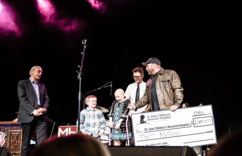 Photo: (l to r) Richard Shadyac Jr., President and CEO of ALSAC, the fundraising and awareness organization for St. Jude Children's Research Hospital; St. Jude patients Ian and Kenlie; iHeartMedia radio personality Bobby Bones and Grammy Award-winning country music artist Garth Brooks on stage for $2 million check presentation.