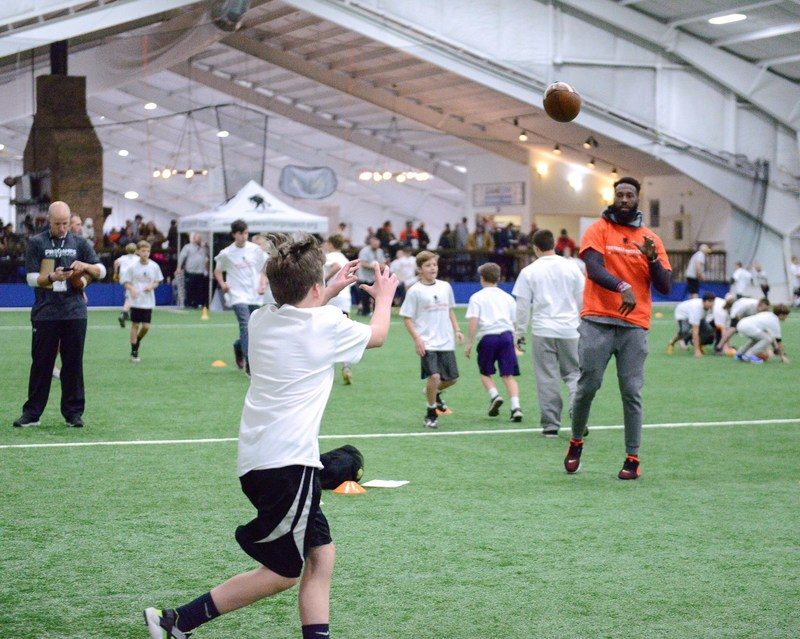 Cincinnati Bengals star Brandon LaFell throws a football to a kid at the Wounded Warrior Project Brandon LaFell Football ProCamp.