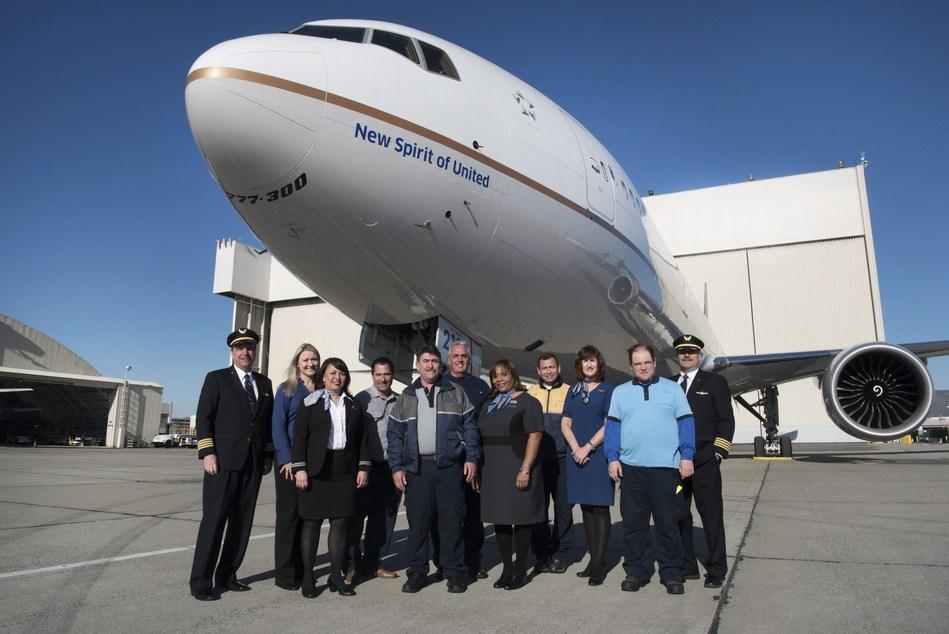 """Employees gather under United's new 777-300ER entitled the """"New Spirit of United""""."""