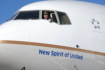"United pilot waves from United's new 777-300ER entitled the ""New Spirit of United""."