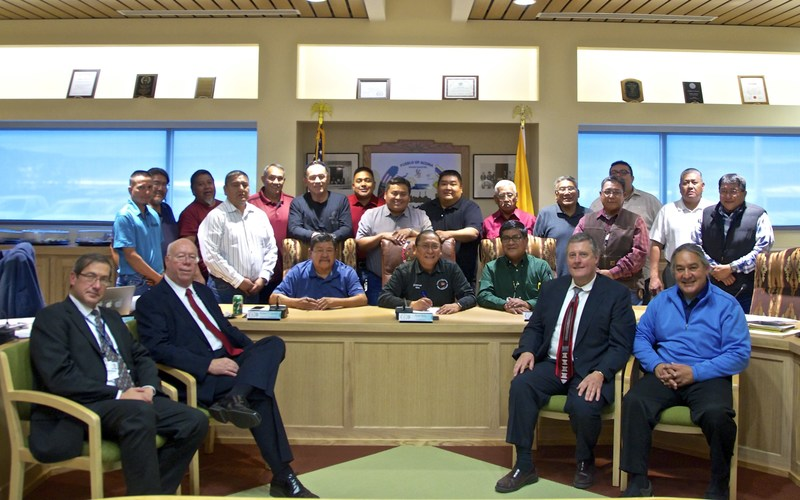 Acoma Pueblo Governor Kurt Riley, surrounded by members of Tribal Council and Acoma Business Enterprises, enthusiastically signs business agreement with Bright Green Group on December 16, 2016.