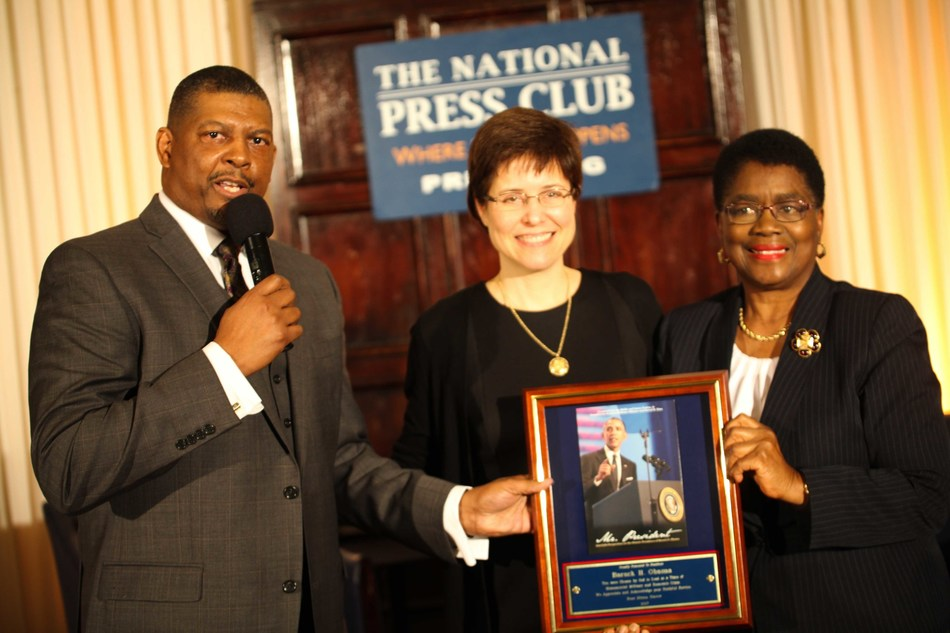 (left to right)  Reverend Darryl D. Sims presents a signed copy of Mr. President to Ms. Melissa Rogers, Special Assistant to President Obama and Executive Director of the White House Office of Faith-Based and Neighborhood Partnerships, with co-collaborator, Dr. Barbara Williams-Skinner, President of Skinner Leadership Institute