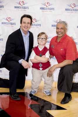Levi, Coach Menzies and Miracle Flights CEO, Mark E. Brown pose for a photo op