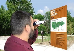 Man using MoJo low vision electronic magnifier to see a sign in the distance.