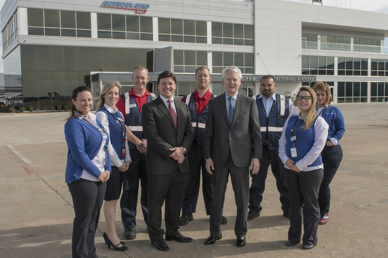 Employees of American Aero FTW, a fixed-base operator (FBO) at Meacham International Airport in Fort Worth, surround general manager Riggs Brown (center left) and owner Robert M. Bass (center right) as the team celebrates the grand opening of the private aviation terminal's new facility, designed to attract travelers from around the country and across the globe.